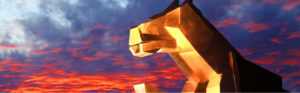 lionlike gold sculpture with sunset background