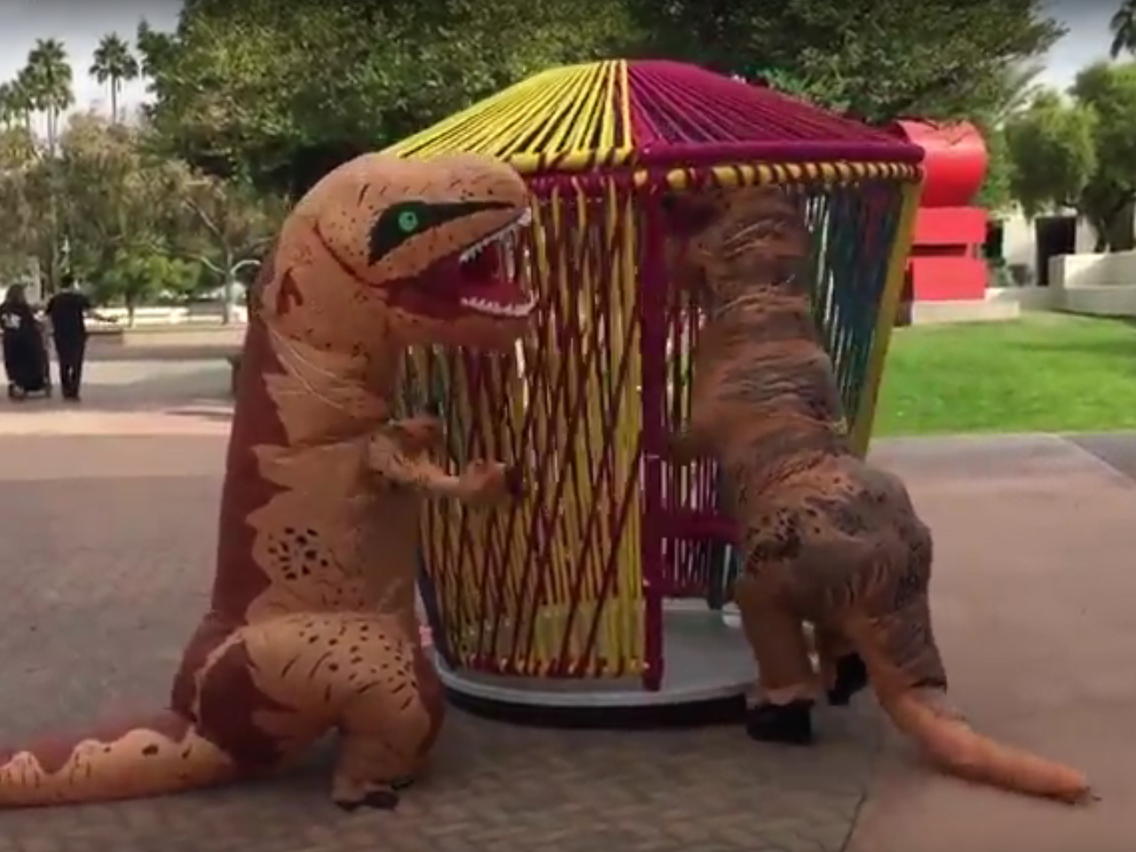 two people in dinosaur costumes interacting with sculptures