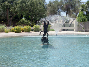 woman and fish sculpture in a pond