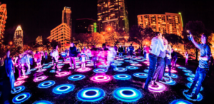 Outdoor art with light up rings on ground with people standing on them